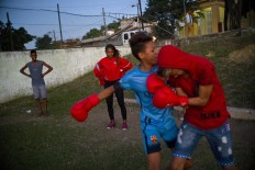 In this Jan. 19, 2017 photo, boxer Idamerys Moreno, center back, looks at children playing around, at a sports center in Havana, Cuba. Boxing has long been an athletic engine for Cuba, which has won 72 Olympic medals in that category but women are not allowed to box. AP/Ramon Espinosa