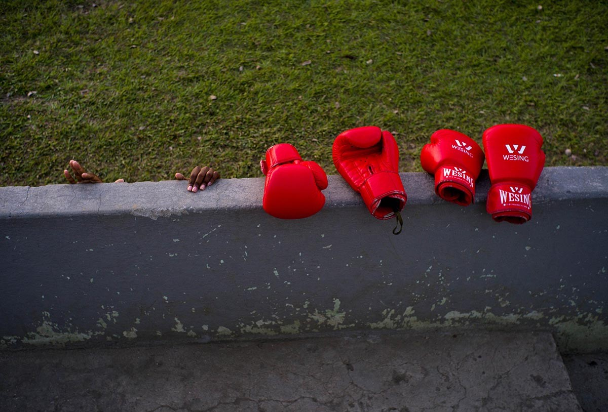 "In this Jan. 19, 2017 photo, boxer Legnis Cala's hands grab a wall, next to boxing gloves during a warm-up prior to a training session, in Havana, Cuba. Officials have said they're analyzing whether to allow women to box and say they are carrying out medical studies to understand the impact of blows to a woman's body and whether such action is ""appropriate."" AP/Ramon Espinosa"