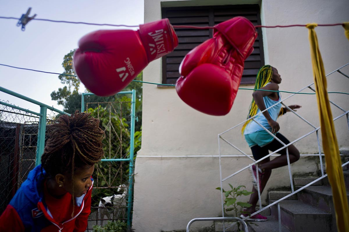 "In this Jan. 19, 2017 photo, boxer Legnis Cala runs up a flight of stairs in the backyard of her house, in Havana, Cuba. ""I see myself at the Olympics in Japan 2020,"" Moreno said. ""That's my dream."" Pictured at bottom left is boxer Idamerys Moreno. AP/Ramon Espinosa"