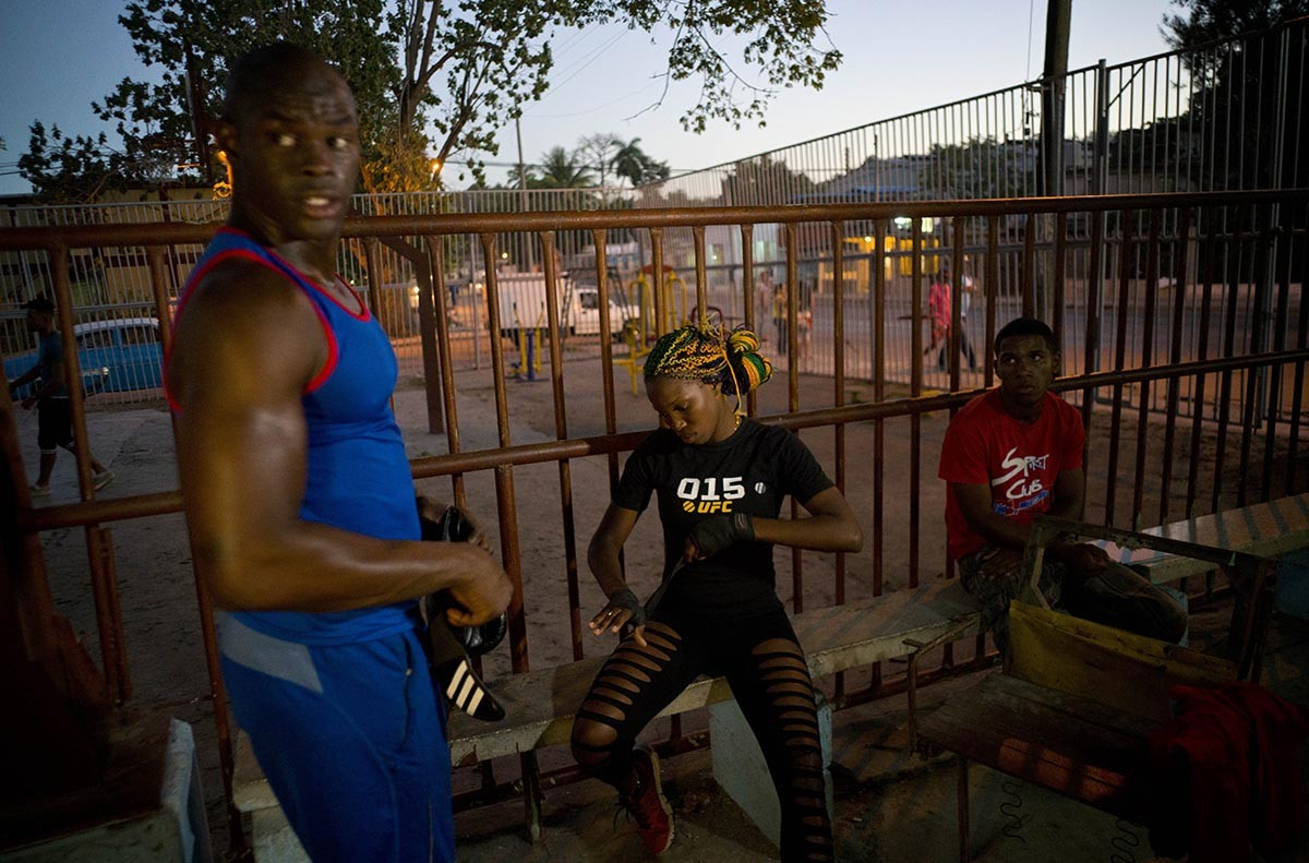 "In this Jan. 24, 2017 photo, Olympic silver medalist Emilio Correa Jr., left, mentors female boxer Legnis Cala, center, at a sports center in Havana, Cuba. ""They can bring more glory to the Cuban sport,"" Correa said. ""They are diamonds in the rough. The motor skills, the explosive nature and the energy of Cuban boxers are also present in these women."" AP/Ramon Espinosa"
