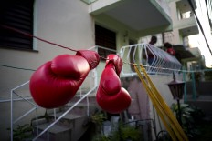 In this Jan. 19, 2017 photo, Idanerys Moreno's boxing gloves hang on a line to dry, after a training session in Havana, Cuba. Women were first allowed to box at the Olympics during the 2012 Summer Olympics but they are still not allowed to box in Cuba. AP/Ramon Espinosa