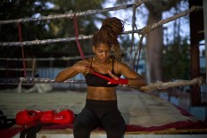 In this Jan. 24, 2017 photo, boxer Idamerys Moreno wraps a bandage on her hand before a training session at a sports center in Havana, Cuba. Boxing has long been an athletic engine for Cuba, which has won 72 Olympic medals in that category but women are not allowed to box. AP/Ramon Espinosa