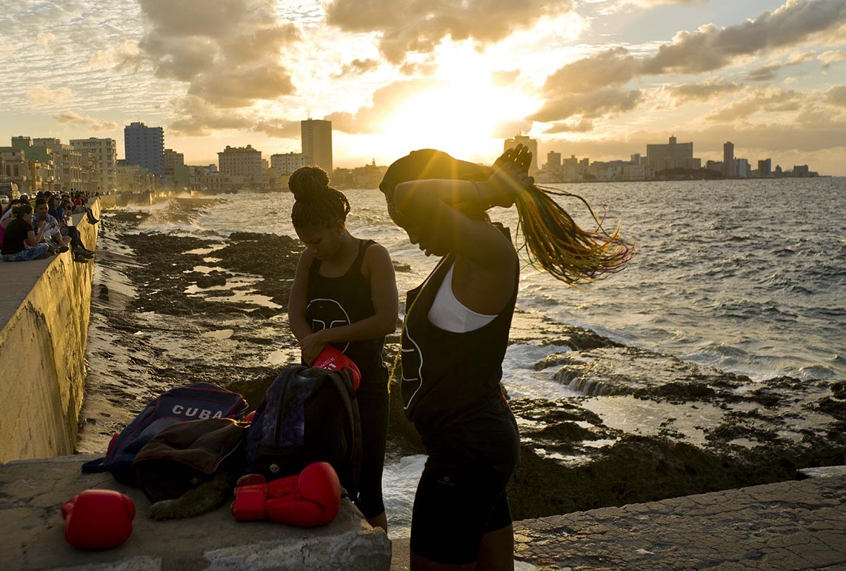 In this Jan. 30, 2017 photo, boxers Idamerys Moreno, left, and Legnis Cala, get ready for a photo session on Havana's Malecon, in Cuba. Moreno trains at least two hours a day after she gets off work, completing a routine that includes running several miles, lifting weights, hitting a punching bag and sparring with both women and men. AP/Ramon Espinosa