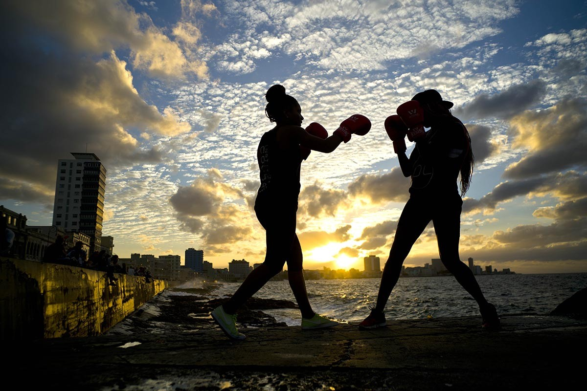 "In this Jan. 30, 2017 photo, boxers Idamerys Moreno, left, and Legnis Cala, train during a photo session on Havana's sea wall, in Cuba. Moreno and Cala are part of a group of up-and-coming female boxers on the island who want government support to form Cuba's first female boxing team and help dispel a decades-old belief once summed up by a former top coach: ""Cuban women are meant to show the beauty of their face, not receive punches."" AP/Ramon Espinosa"