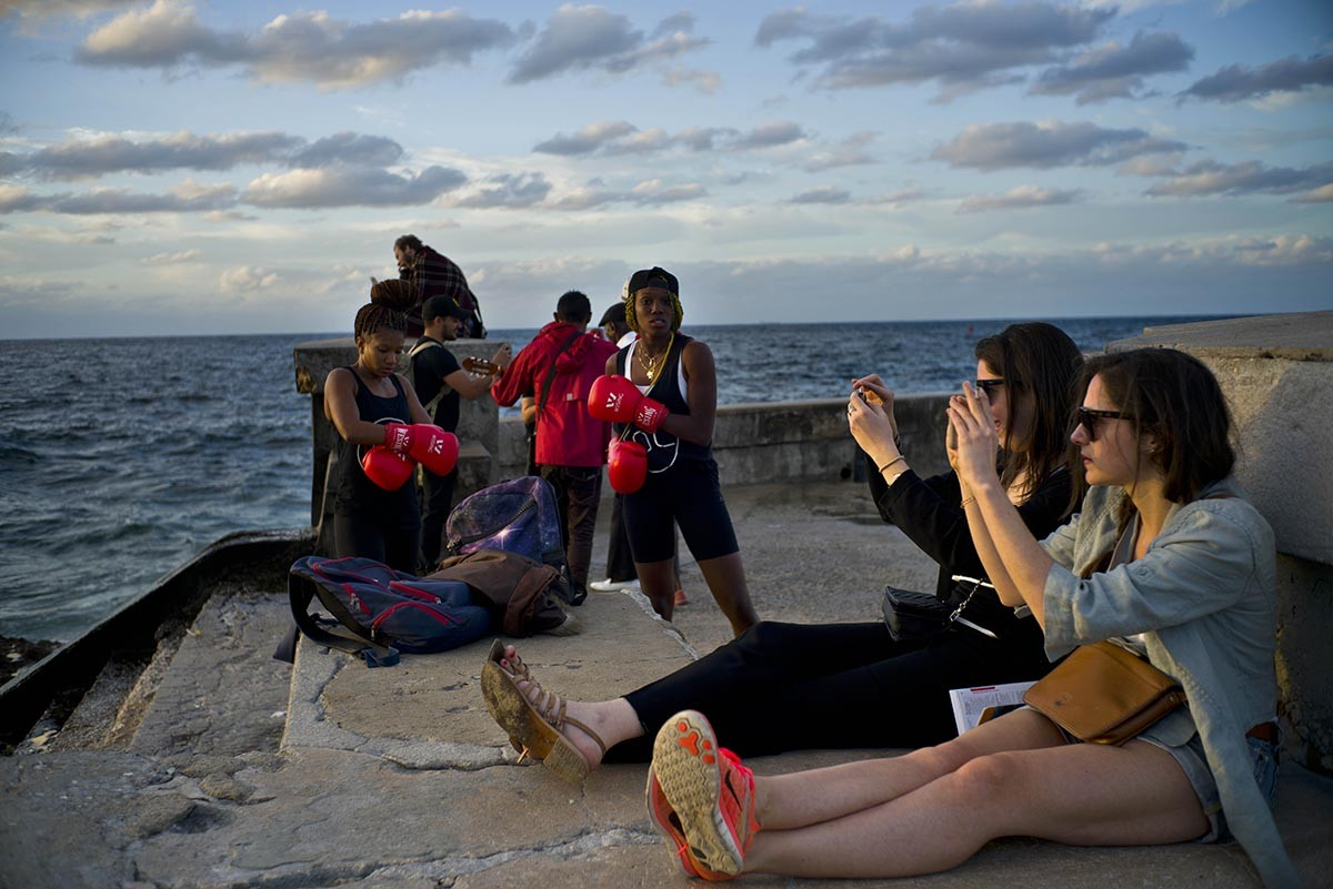 In this Jan. 30, 2017 photo, boxers Idamerys Moreno, left, and Legnis Cala, get ready for a photo session, as tourists take photos of the sunset, on Havana's sea wall in Cuba. Female athletes in Cuba have made strides in many other sports, including wrestling, judo and most recently, weightlifting, but not in boxing. AP/Ramon Espinosa