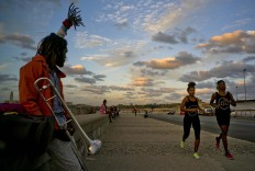 "In this Jan. 30, 2017 photo, boxers Idamerys Moreno, second right, and Legnis Cala, right, run along Havana's Malecon, in Cuba. Moreno and Cala are part of a group of up-and-coming female boxers on the island who want government support to form Cuba's first female boxing team and help dispel a decades-old belief once summed up by a former top coach: ""Cuban women are meant to show the beauty of their face, not receive punches."" AP/Ramon Espinosa"