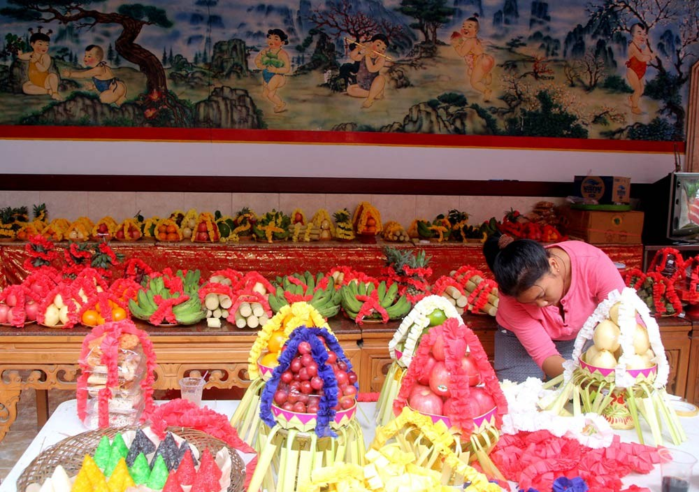 A woman decorates offerings comprising fruit and cakes at Darmayana Temple in Kuta, Bali, on Jan. 25. JP/ Zul Trio Anggono