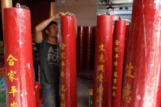 A temple worker places a sticker containing prayer writings on a giant red candle at Dharma Ramsi Temple in Bandung, West Java, ahead of Chinese New Year. Congregation members of the temple can order giant red candles to burn for their individual prayers. JP/Arya Dipa