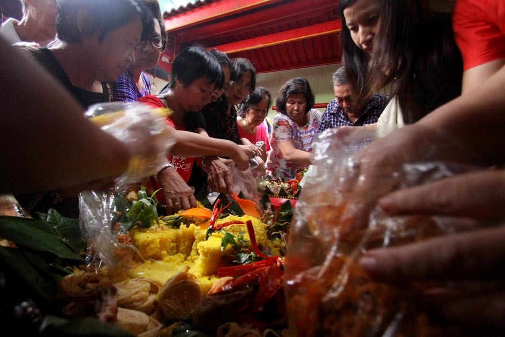 Congregation members of Poncowinatan Temple in Yogyakarta use the Javanese dish tumpeng during their prayers. Tumpeng, a cone of yellow rice with various sides, is used in the ritual to display the acculturation of Chinese and Javanese cultures. JP/Aditya Sagita