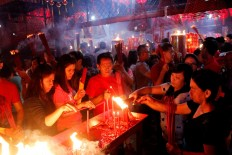 Men and women burn candles during prayers at Toasebio Dharma Jaya Temple in West Jakarta on the eve of Chinese New Year on Jan. 27. JP/Bimo Rahardjo