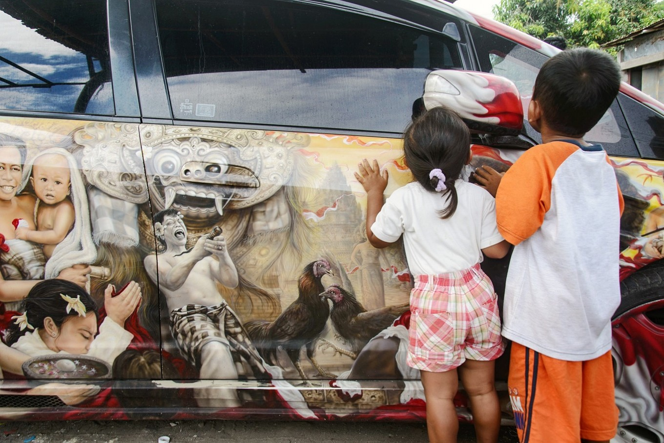 Curious: Children look inside an artfully-decorated car near the cockfighting arena.