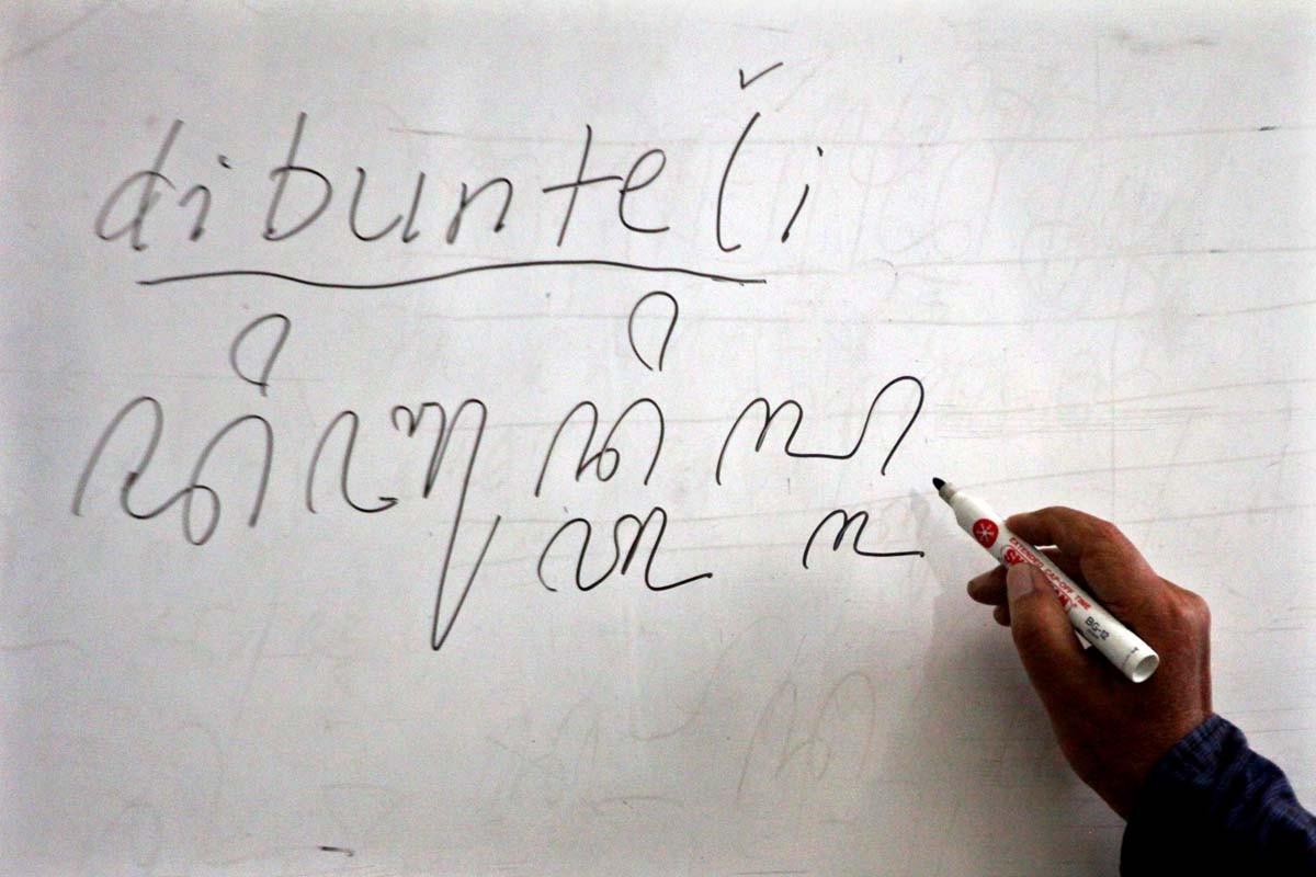 A teacher writes the word dibunteli (wrapped) in Javanese script on a white board. JP/ Aditya Sagita