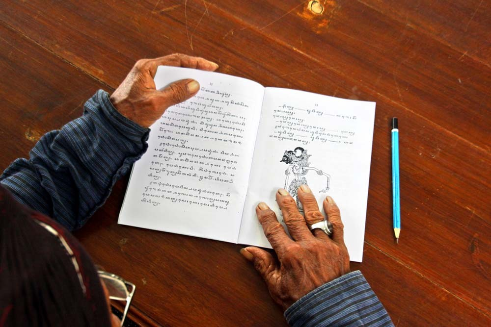 A servant opens a textbook on a page containing excepts of a wayang story. JP/ Aditya Sagita