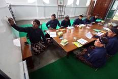 Participants of a class listen to the teacher, KRT Rinta Iswara, who explains the technique of writing Javanese script. JP/ Aditya Sagita