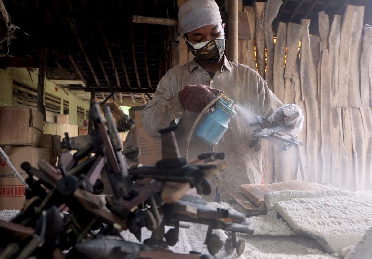 A worker sprays a clear coating onto a classic airplane miniature. JP/ Ganug Nugroho Adi