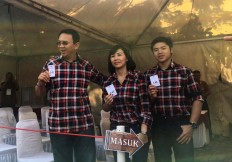 "Jakarta gubernatorial candidate number 2 and incumbent Governor Basuki ""Ahok"" Tjahaja Purnama, wife Veronica Tan and son Nicholas Sean Purnama show their ballots during the election in South Jakarta on Wednesday, Feb. 15, 2017. JP/Nurul Fitri Ramadhani"