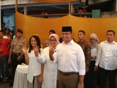 Jakarta gubernatorial candidate number 3 Anies Baswedan with his wife and daughter show their inked fingers after voting in South Jakarta on Wednesday, Feb. 15, 2017. JP/ Indra Budiari