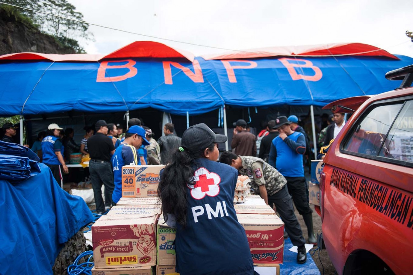An Indonesian Red Cross worker stands in front of a National Disaster Mitigation Agency (BNPB) rescue post in Songan village, Kintamani, on Monday, February 13, 2017. JP/ Anggara Mahendra