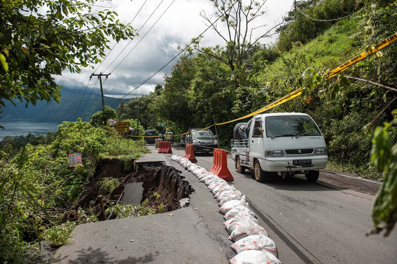 Vehicles pass a road heading to Songan village that was partially affected by a landslide on Monday, February 13, 2017. JP/ Anggara Mahendra