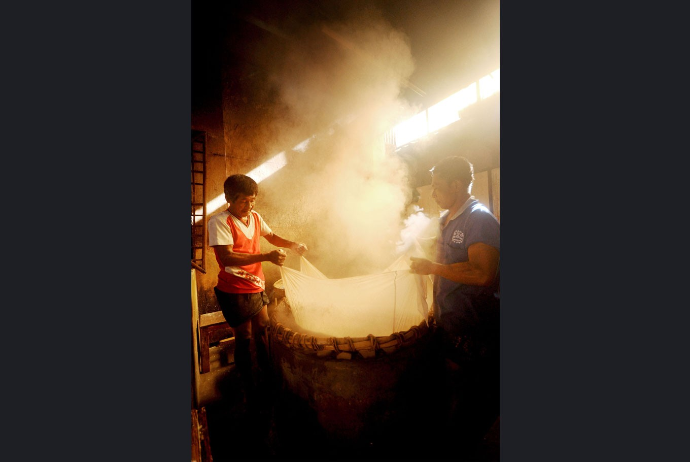 Soybean heat: Two workers sieve boiled soybean pulp in a large basin over burning firewood.