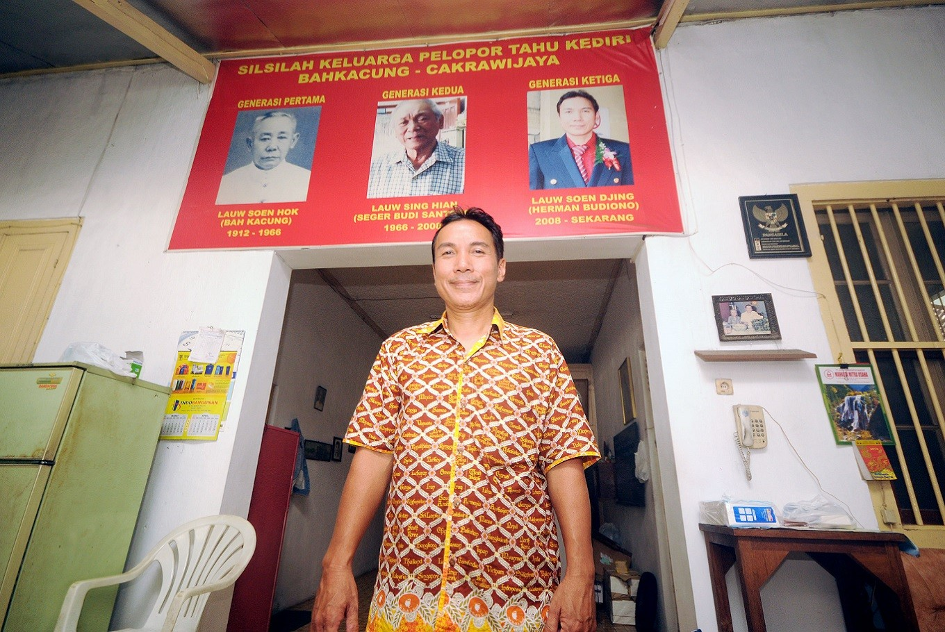 Third generation: Herman Budiono poses with a poster of his father and grandfather at his modest shop that also serves as tofu factory.