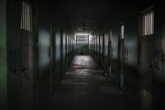 In this Feb. 2, 2017 photo, an inmate sits facing the wall at the end of a corridor between cells at the Monte Cristo agricultural penitentiary in Boa Vista, Brazil. Some prisoners serving time for lesser crimes were forced to participate in gang-driven slaughters that left at least 130 inmates dead in January at this jail, and one other. AP Photo/Felipe Dana