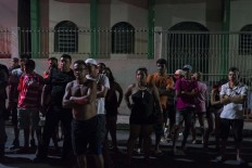 In this Feb. 5, 2017 photo, residents watch police work at a crime scene where a man was murdered in Manaus, Brazil. The increasingly violent city is a thoroughfare for drug trafficking across South America, where authorities suspect most murders are gang related. AP Photo/Felipe Dana