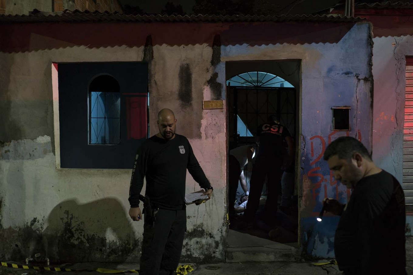 In this Feb. 5, 2017 photo, police inspect a home where a murder victim lies on the floor in Manaus, Brazil. The increasingly violent city is a thoroughfare for drug trafficking across South America, where authorities suspect most murders are gang related. AP Photo/Felipe Dana
