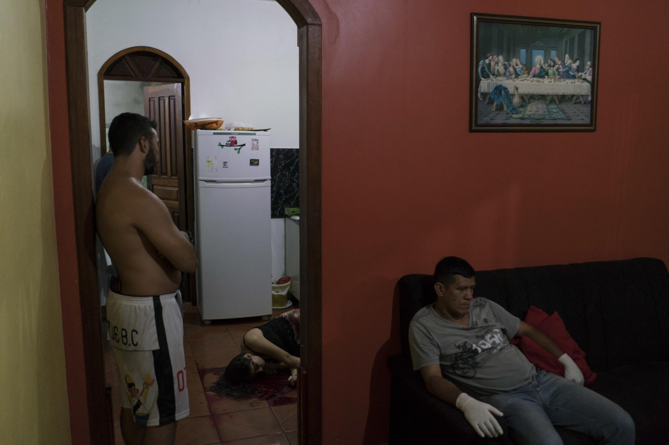 In this Feb. 5, 2017 photo, a gloved morgue worker rests at a home where the body of a woman lies on the kitchen floor after she was shot to death under unclear circumstances in Manaus, Brazil. The increasingly violent city is a thoroughfare for drug trafficking across South America, where authorities suspect most murders are gang related. AP Photo/Felipe Dana