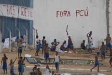 In this Jan. 20, 2017 file photo, inmates walk amid tension as confrontation between rival gangs continue in the Alcacuz prison in Nizea Floresta, near Natal, Brazil. The violence and the grisly killings go beyond the typical problems in Brazil's prisons and could signal the beginning of a nationwide gang war for control of the system, said Benjamin Lessing, a political scientist at the University of Chicago who studies criminal conflict in Latin America. At Alcacuz, the First Capital Command gang is fighting the Crime Syndicate for control. AP Photo/Felipe Dana, File