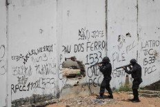 In this Jan. 21, 2017 file photo, Special Operations Battalion Police officers enter the Alcacuz prison amid tension between rival gangs in Nisia Floresta, near Natal, Brazil. Brazil incarcerates more than 620,000 people in a system that has space for a little over 370,000, according to a 2014 Ministry of Justice report. Forty percent of detainees are merely awaiting trial. AP Photo/Felipe Dana, File