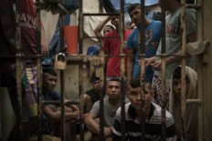 In this Feb. 6, 2017 photo, detainees crowd a holding cell at a police station near Manaus, Brazil. The beginning of the chain that feeds Brazilian gangs are improvised cells at police stations, where 10 percent of Brazil's more than 600,000 inmates await trial. AP Photo/Felipe Dana