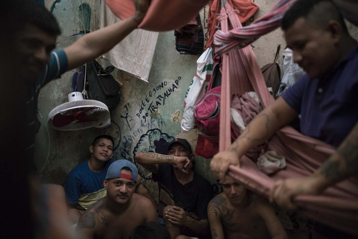 In this Feb. 6, 2017 photo, detainees sit inside an overcrowded cell at a police station near Manaus, Brazil. The walls are filled with infiltrations of moisture, the poor construction of the roof let almost no light shine inside and inmates put hammocks one on the top of the other, while one prisoner slept in the open bathroom. AP Photo/Felipe Dana