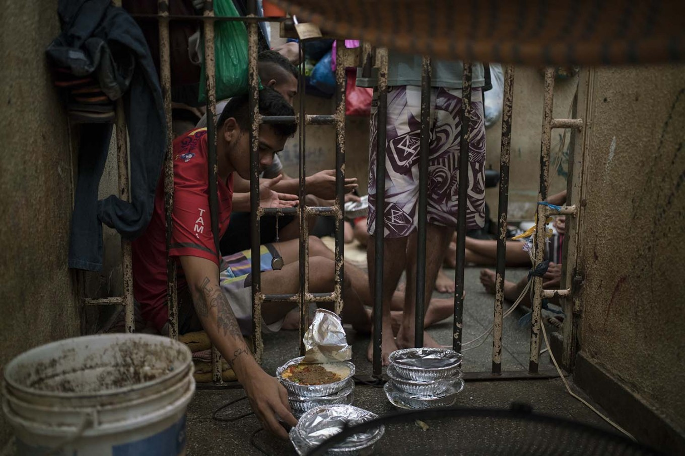 In this Feb. 6, 2017 photo, an inmate reaches for a plate of food during lunchtime inside an overcrowded cell at a police station near Manaus, Brazil. The business strategy of Brazilian crime gangs is to dominate overcrowded prisons, then control the streets. AP Photo/Felipe Dana