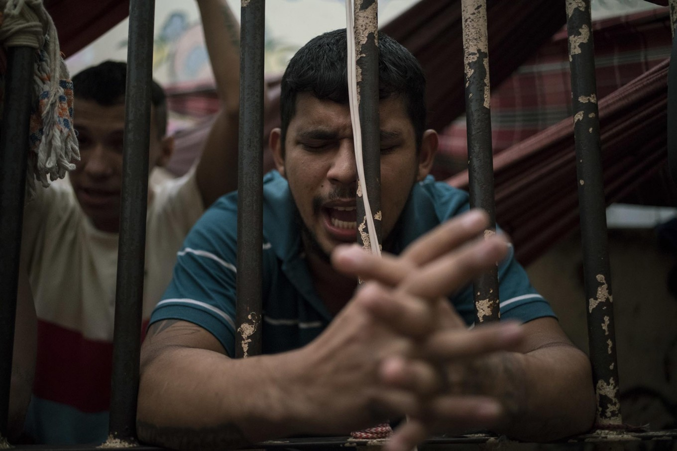 In this Feb. 6, 2017 photo, a detainee prays inside an overcrowded cell at a police station near Manaus, Brazil. All 24 detainees being held in this space made for eight said they hoped to avoid being transferred to a bigger prison under gang rule. AP Photo/Felipe Dana