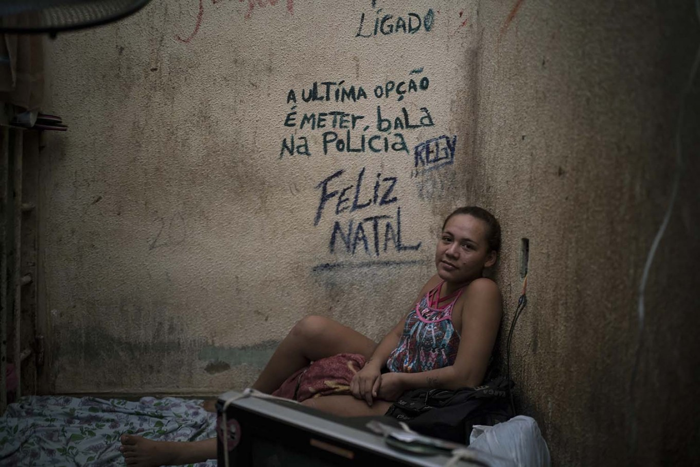 "In this Feb. 6, 2017 photo, female prisoner Regiane sits on her bed inside a corridor between two cells crowded with men at a police station near Manaus, Brazil. The message on the wall reads in Portuguese: ""The last option is to put a bullet in the police. Merry Christmas."" AP Photo/Felipe Dana"