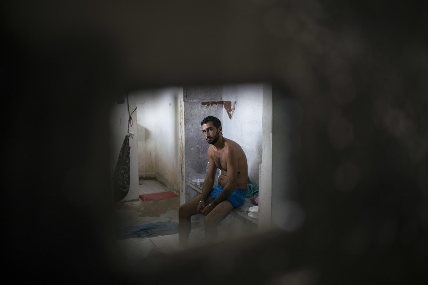 In this Feb. 2, 2017 photo, an inmate sits inside a cell separated from the main prison population, at the Monte Cristo agricultural penitentiary in Boa Vista, Brazil. Many inmates shouted that they need medical attention. AP Photo/Felipe Dana