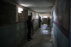 In this Feb. 2, 2017 photo, guards stand outside prison cells at the Monte Cristo agricultural penitentiary in Boa Vista, Brazil. Guards, administrative prison staff and families of inmates of this prison said gang leaders ordered newcomers to join killing sprees in January and dismember and behead the dead. AP Photo/Felipe Dana
