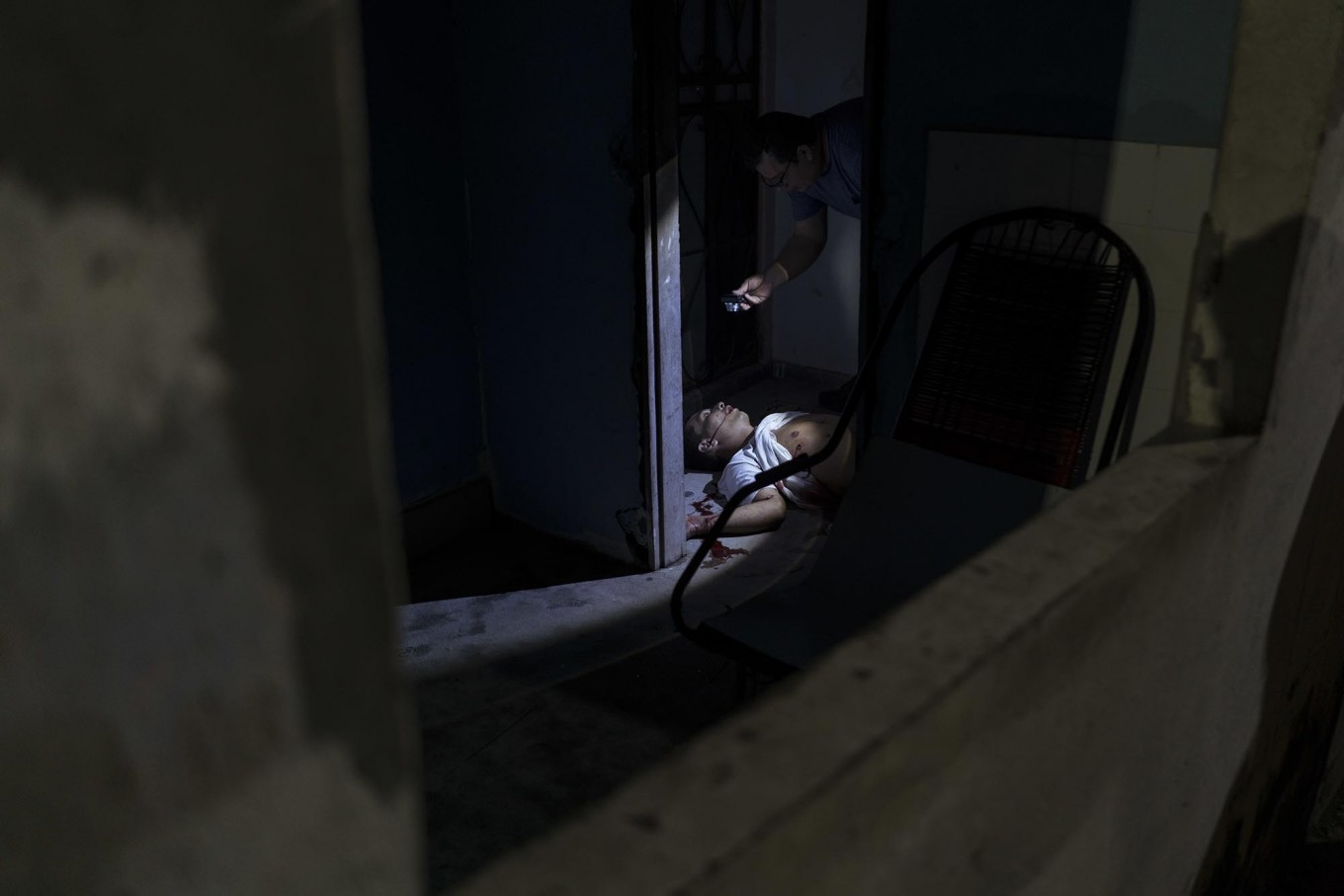 In this Feb. 5, 2017 photo, police inspect a murder victim on the floor of a home in Manaus, Brazil. The increasingly violent city is a thoroughfare for drug trafficking across South America, where authorities suspect most murders are gang related. AP Photo/Felipe Dana