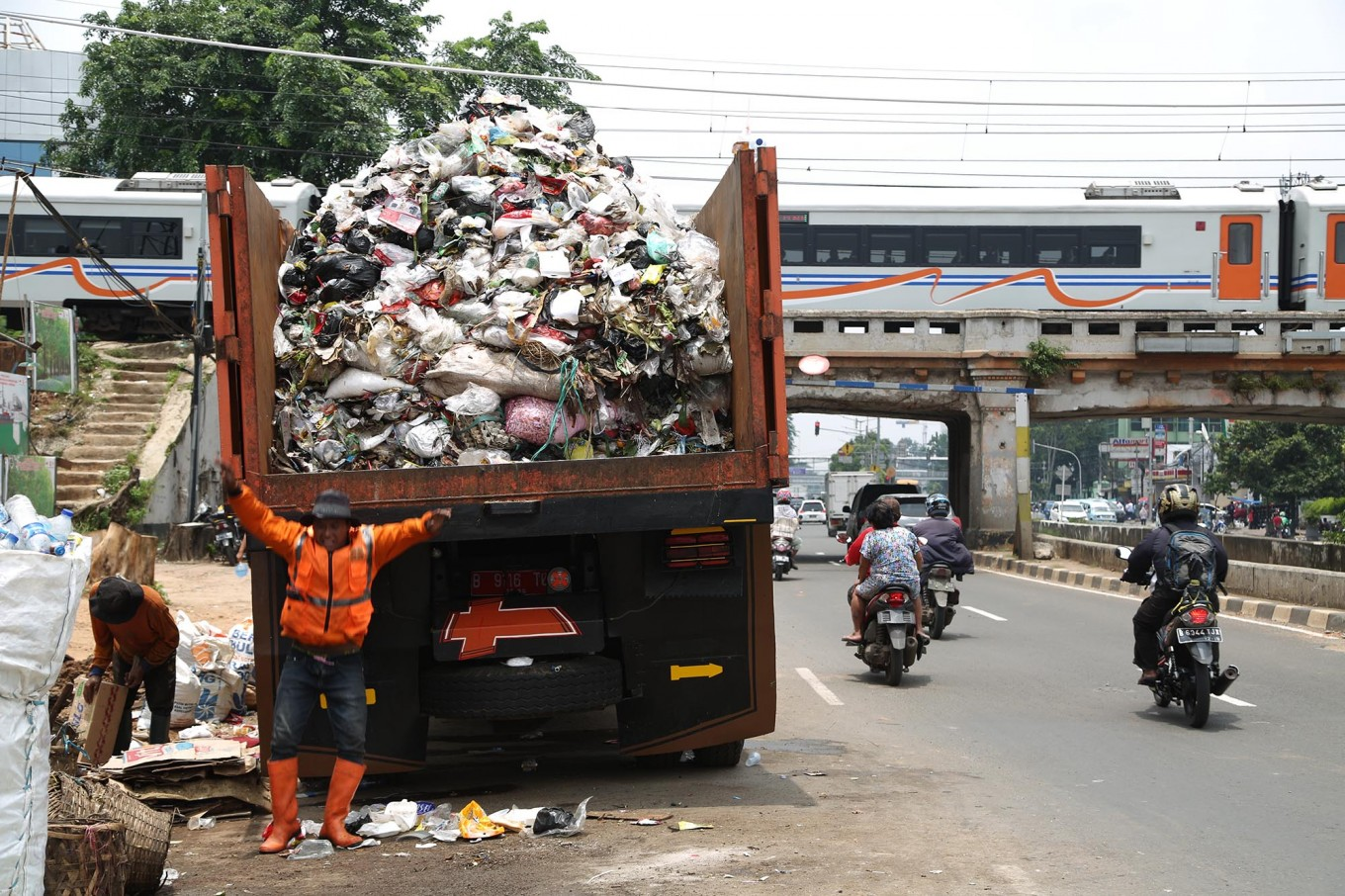 A worker jumps from a garbage truck to collect garbage from Jl. Jatinegara Barat in East Jakarta on Feb. 28, 2017. (JP/PJ Leo)