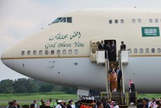 King Salman bin Abdulaziz Al Saud rides down the electric stairs to disembark from his plane after his arrival at Halim Perdanakusuma Airport in Jakarta, on Wednesday. JP/Dhoni Setiawan