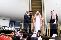 King Salman (center) adjusts his headscarf as he reaches the bottom of the stairs upon his arrival at Halim Perdanakusuma Airport. The Saudi king arrived in the world's largest Muslim-majority nation on Wednesday as a part of a month-long Asian tour aimed at boosting economic ties with the continent's states. JP/Dhoni Setiawan