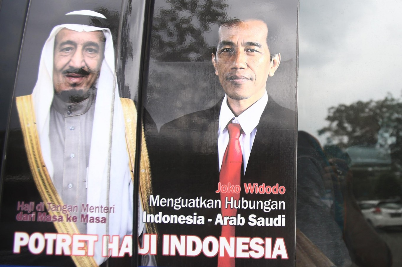 "A poster of King Salman bin Abdulaziz Al Saud and President Joko ""Jokowi"" Widodo hangs in a window at Halim Perdanakusuma Airport. JP/Dhoni Setiawan"