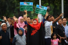 Carrying banners, Indonesian women greet King Salman bin Abdulaziz Al Saud upon his arrival at Halim Perdanakusuma Airport in East Jakarta on Wednesday. JP/Dhoni Setiawan