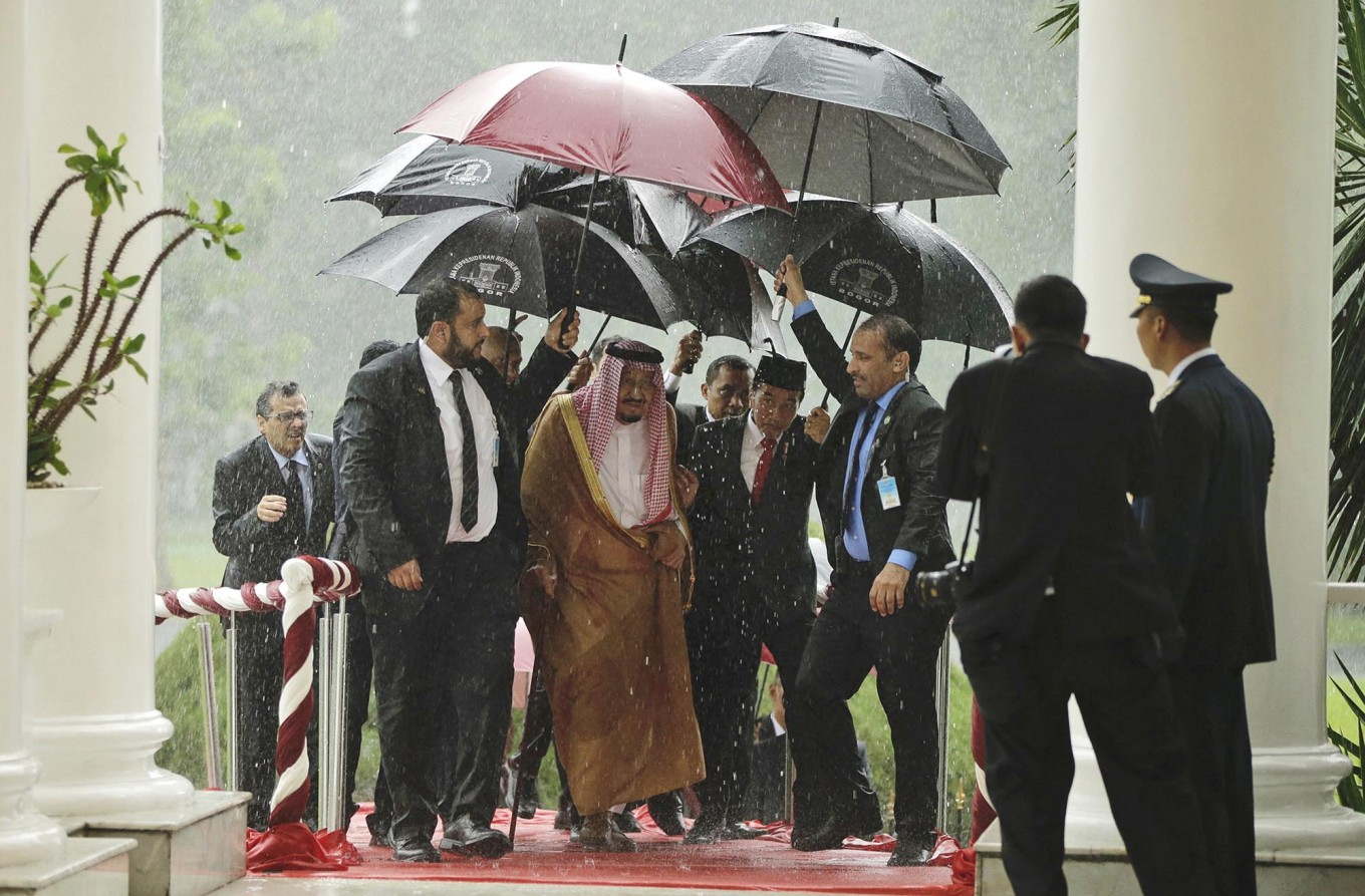 """King Salman (second left) and Indonesian President Joko """"Jokowi"""" Widodo (center) walk under umbrellas during heavy rain at the Presidential Palace in Bogor, West Java, on March 1. Salman arrived in the world's largest Muslim-majority nation on Wednesday as a part of a multi-nation tour aimed at boosting economic ties with Asia. AP/Pool/Achmad Ibrahim"""
