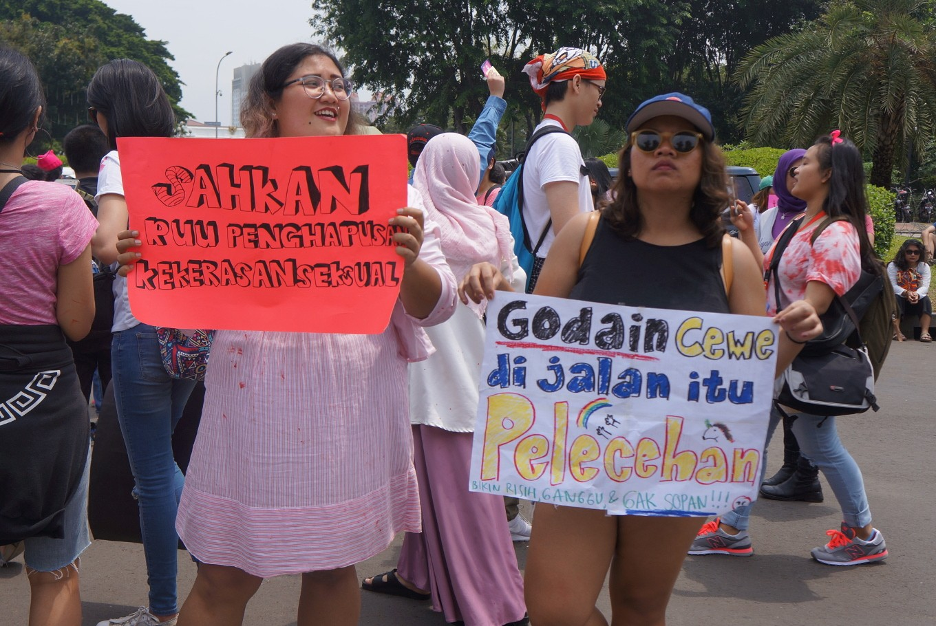 Two women hold posters encouraging the government to legalize a law to eliminate sexual violence (left) and informing people that catcalling is a form of sexual harassment.
