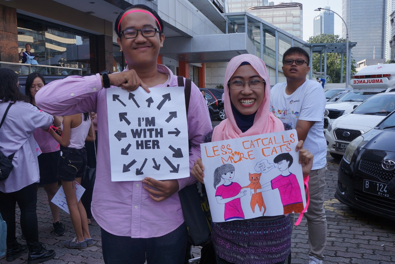 Two participants show their support for women's rights and against catcalling during the march.