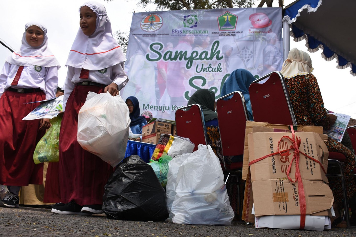 Primary school students and residents bring recyclable trash to get free healthcare services that could cover BPJS Kesehatan premiums. JP/Aman Rochman