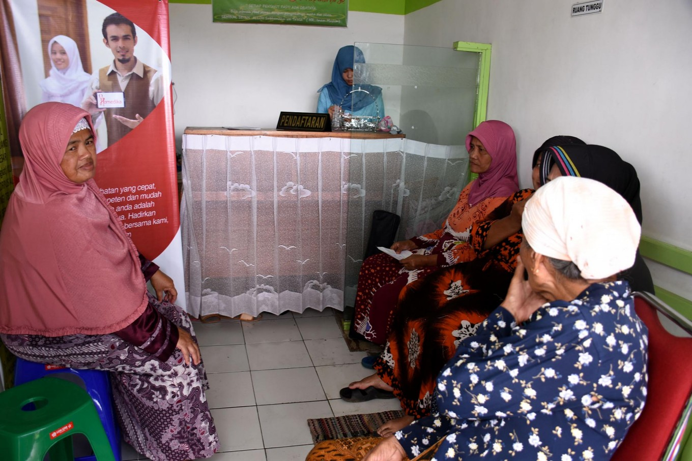 Residents queue for drugs to be distributed during a healthcare program in the Indonesia Medika Clinic Malang, East Java, on Tuesday (21/2). JP/ Aman Rochman