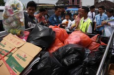 A staff member weighs the trash from residents, during the healthcare program in Indonesia Medika Malang, East Java, on Tuesday (21/2). The clinic's healthcare program is a collaborative effort between BPJS Kesehatan, the Malang Environment Agency, students and residents. JP/Aman Rochman